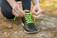 Girl in sports pants and hoodie, sitting tying shoelaces on spor Royalty Free Stock Images