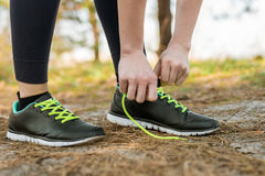 A girl in sports pants and a hoodie, standing tied up her shoela Royalty Free Stock Images