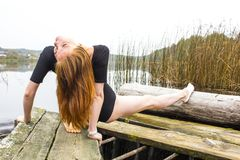 Girl with sports sexy figure on background of calm autumn river. Yoga, Meditation, Relax. Girl with a sports sexy figure is engaged in sports yoga stretching Royalty Free Stock Photos
