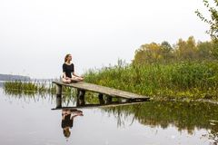 Girl with sports sexy figure on background of calm autumn river. Yoga, Meditation, Relax. Girl with a sports sexy figure is engaged in Meditation, relaxation Royalty Free Stock Photography