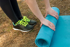 Girl in sports shoes spreads blue karemat in nature, for yoga, w Stock Photography