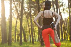 Girl sports. stretching. running in the forest stock images