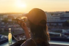 A girl in a sports suit holds a huge piece of pizza and bottle of mojito on the sunset city background. Concept royalty free stock images