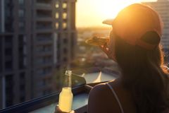 A girl in a sports suit holds a huge piece of pizza and bottle of mojito on the sunset city. Background. Concept royalty free stock photography