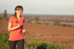 Girl in a sports suit runs along the field Stock Photo