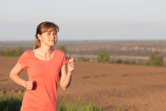 Girl in a sports suit runs along the field Royalty Free Stock Image