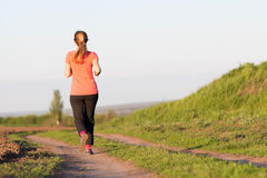 Girl in a sports suit runs along the field Royalty Free Stock Photos