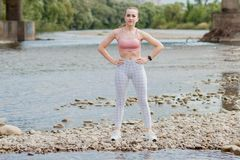Girl in sports uniforms makes a stretch on the river bank