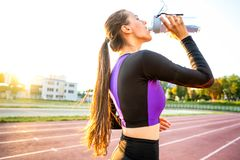 Girl sportsman crossfit and squats agains and drinks water at sunset.  royalty free stock images