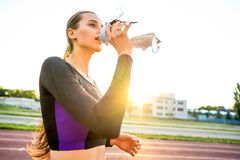Girl sportsman crossfit and squats agains and drinks water at sunset.  royalty free stock photos