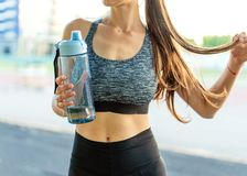 Girl sportsman crossfit and squats agains and drinks water at su stock photo