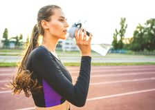 girl sportsman crossfit and squats agains at sunset in the stadium drink water royalty free stock photo