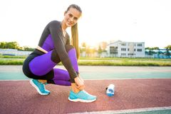 Girl sportsman crossfit and squats agains at sunset in the stadium drink water.  stock photo