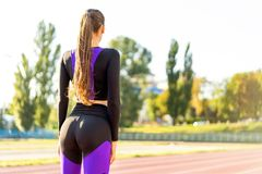 Girl sportsman crossfit and squats agains at sunset in the stadium.  royalty free stock photos