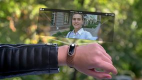 Girl sportsman hand call friend who appears in hologram. Smart watch futuristic and technological. Green Park in stock video