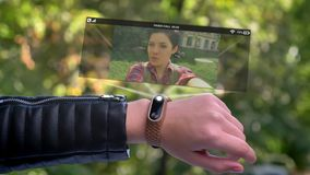 Girl sportsman hand call friend who appears in hologram. Smart watch futuristic and technological. Green trees in stock video