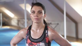 Girl sportsman after a hard workout. Hands on the belt. Enters the frame and lifts her gaze from the floor upstairs to the camera. stock footage