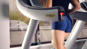 Girl with sportswear ass training on a treadmill. Slow motion. stock footage