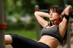 Girl in sportswear doing push-ups with hands behind head Stock Image