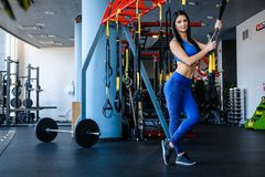 Beautiful girl in sportswear holding functional loops, posing in modern fitness club. Girl in sportswear holding functional loops, posing in modern fitness club stock images