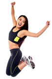 Girl in sportswear jumping with joy Stock Photography