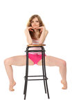 Girl in sportswear leans against  bar stool. On white background Royalty Free Stock Photo
