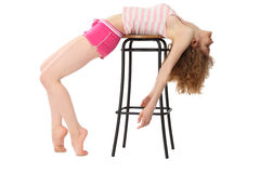 Girl in sportswear lies on bar stool Royalty Free Stock Photo