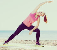 Girl in sportswear practice  yoga at sea beach Royalty Free Stock Images