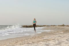 Girl in sportswear running along the surf line. Early morning.  Stock Image