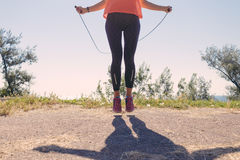 Girl in sportswear and sneakers jumping with a skipping rope on. In the summer of the sea background, toned image Royalty Free Stock Photos
