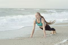 Girl in sportswear standing in a bar on the beach, waves in the. Background stock photos