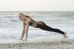 Girl in sportswear standing in a bar on the beach, waves in the. Background stock image