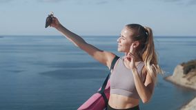 Girl in sportswear takes selfie on phone after training, shows gesture of peace. Sportswoman takes pictures of herself on smartphone with beautiful ocean view stock video footage