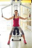 Girl in sportswear is working out on butterfly machine in gym Royalty Free Stock Image