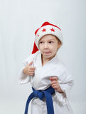 Girl sportswoman in a kimono and beanie Santa Claus Stock Photos