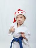 Girl sportswoman in a kimono and beanie Santa Claus Stock Photos