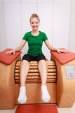 Girl in sportwear on relax massage equipment healthy spa salon Royalty Free Stock Images