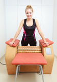 Girl in sportwear using relax massage equipment healthy spa salon Stock Images