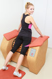 Girl in sportwear using relax massage equipment healthy spa salon Stock Photos