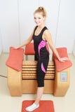 Girl in sportwear using relax massage equipment healthy spa salon Stock Photos