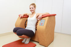 Girl in sportwear using relax massage equipment healthy spa salon Royalty Free Stock Photography