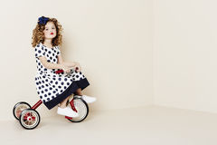 Girl in spots on red tricycle Stock Photos