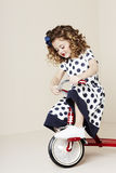 Girl in spots on retro tricycle Stock Photography