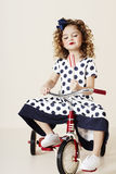 Girl in spots on tricycle Royalty Free Stock Images