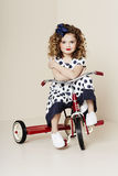 Girl in spots on tricycle Royalty Free Stock Photography