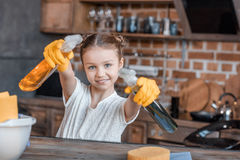 Girl with spray bottles and different cleaning supplies at home Royalty Free Stock Image