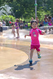 Girl in spray pad. Girl running in water spray pad Royalty Free Stock Image