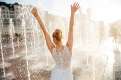 Girl in a spray of water in a fountain stock photography
