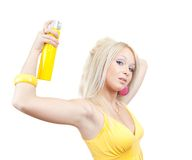 Girl spraying hair lacquer onto her hair. Blonde girl spraying hair lacquer onto her hair, isolated over white Royalty Free Stock Images
