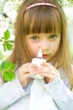 Girl spraying medicine in nose. Little girl spraying medicine in nose, nose drops, nose spray Stock Images